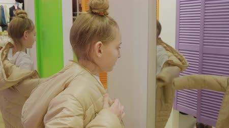 seçme : Young girl trying beige jacket front mirror while shopping in fashion showroom. Teenager girl looking to mirror to new jacket in clothes store Stok Video