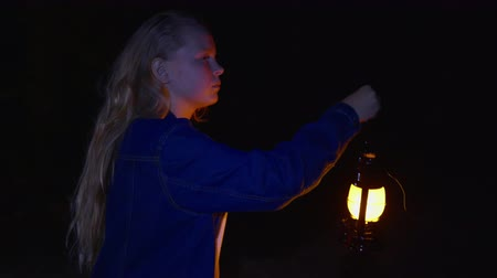 indicating : Teenager girl with oil lamp in dark in summer forest. Tourist girl with kerosene lamp walking on dark woodland at night walk Stock Footage