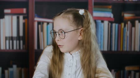 boekenplank : Portrait schoolgirl in round spectacles with two hair tail on bookshelf background. School girl in glasses on bookcase background in class room talking on lesson