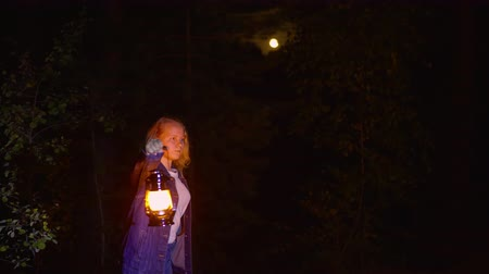 lampa naftowa : Young woman with kerosene lantern in scary forest at night on full moon in sky landscape. Scared girl with oil lamp lighting dark woodland at moonlight night