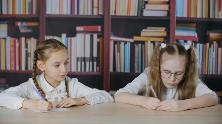 lesson : Schoolgirl looking to classmate notebook at school test on bookcase background. Tricky school girl peeking answer at exam in classroom Stock Footage