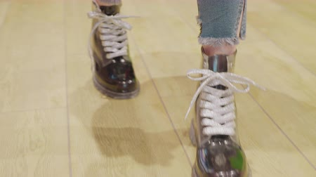 Close-up view of girl in stylish shoes walking on wooden floor. Cropped shot of female feet in fashionable trendy shoes walking indoors Stock Footage