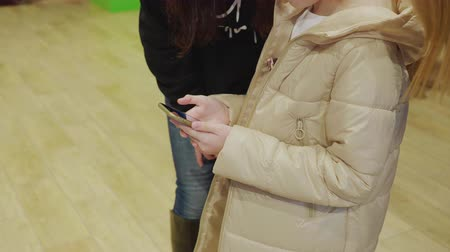 Cropped shot of girl in winter jacket using smartphone indoors. Mid section of adorable child in warm clothes standing indoors and using mobile phone