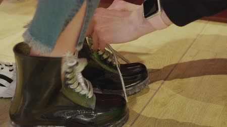 Cropped shot of woman tying shoelaces on boots on female feet. Close-up partial view of young girl wearing stylish trendy shoes while shopping