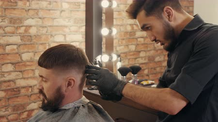 Barber cutting hair to bearded male client in barbershop. Hairdresser holding scissors and grooming handsome client in barber shop