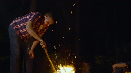 ontvlambaar : Man holding wood stick and touch burning campfire at night. Low angle view of middle aged man in checkered shirt holding wooden club and flaming bonfire in forest at night time