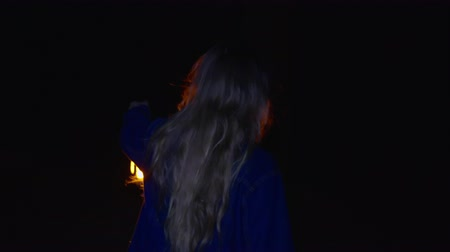 lampa naftowa : Back view of girl holding kerosene oil lamp and walking in dark forest at night. Rear view of teenage girl holding vintage lantern and walking in mysterious darkness at night time Wideo