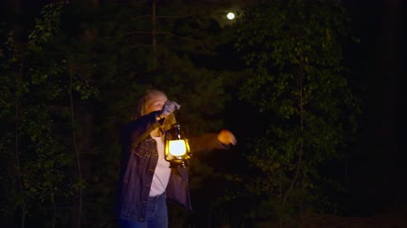 sprookje : Scared young girl holding oil lamp and looking at something in dark forest at night. Frightened teenage girl holding vintage lantern while standing dark forest at night time. Nightmare horror concept Stockvideo