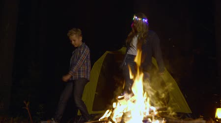 kamp ateşi : Cute happy teenagers dancing near campfire at night time. Low angle view of teenage boy and girl standing near yellow tent in camping and dancing near bonfire at night