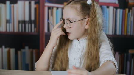 yazarak : Cute focused schoolgirl correcting round glasses writing and talking in classroom. Adorable concentrated teenage girl in spectacles sitting at desk and writing with pen in library Stok Video