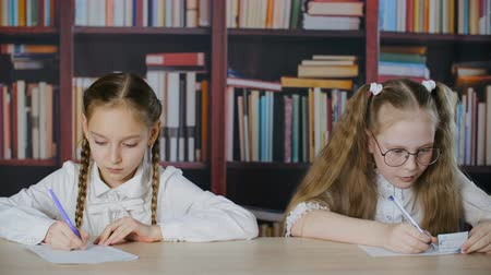 spieken : Focused schoolgirls writing exam and cheating cheat sheet in classroom. Bookshelf background. Adorable teenage girls sitting at desk, talking and cheating during exam in school