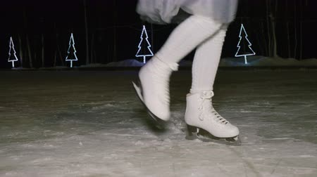 Cropped shot of girl dancing on skating rink at night time. Close-up partial view of girl in skirt and skates dancing and having fun on skating rink in the evening at wintertime