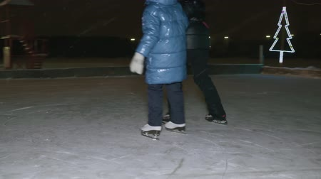 arka görünüm : Back view of mother with child skating on ice at night time. Rear view of mother with kid holding hands and ice skating on skating rink during snowfall in the evening Stok Video