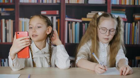 sınıf arkadaşları : Funny schoolgirls bloggers writing on paper and using smartphone in classroom vlog. Adorable funny classmates studying and blogging via cell phone in library Stok Video