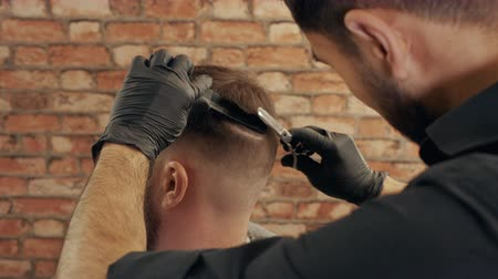 schnurrbart : Close-up view of barber cutting hair to male client in barbershop. Young hairdresser holding comb with scissors and grooming handsome client in barber shop