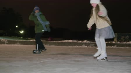 Happy boy and girl teenagers fast skating on ice rink at winter dark park. Smiling sister and brother in speed skates skating in outdoor winter rink at night