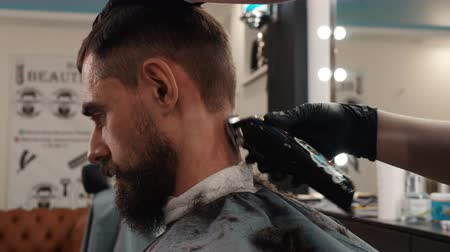 kapster : Portrait hipster man with beard receiving neck shave with electric trimmer. Hairstylist shaving hair on male neck by electric machine in barber salon. Male hairdressing in barbershop