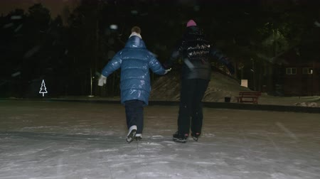 Mom together daughter skating on skates on night ice rink in winter park while snowfall. Mother and girl teenager holding hands while riding on ice skates on outdoor winter rink Dostupné videozáznamy
