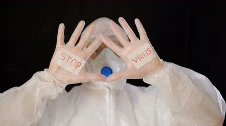 антибиотик : Virologist in white protective suit, mask and gloves showing stop virus on black background. Bioengineer with words on hands stop virus. MERS Chinese infection, atypical pneumonia concept