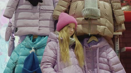 выбирать : Cute little girl posing in front of jackets. Nice girl fitting new winter clothing while standing in store. Shopping concept