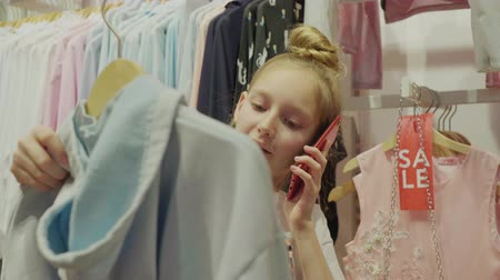 seçme : Cute little girl talking on phone while choosing clothing. Cropped shot of lovely stylish child searching new clothing. Shopping concept