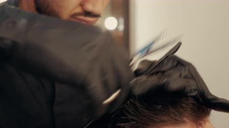 Barber combing hair with hairbrush and cutting with scissors in male salon. Male hipster hairstyle in barbershop. Close up male hairdressing with hair accessories Stock Footage