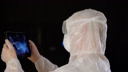 helezon : Bioengineer looking DNA results in tablet pc. Virologist in protective suit and mask holding digital tablet for research. Medical clinical test on digital equipment