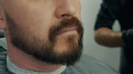 Close up face handsome man while shaving beard with electric razor in barber salon. Bearded man getting trimming beard with shaver in male salon. Stylish shaving hipster man Stock Footage