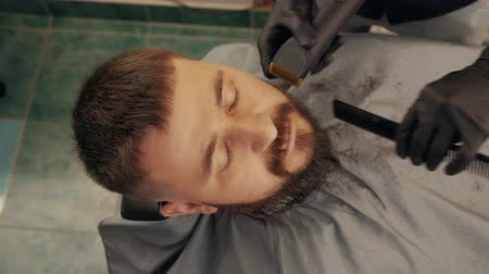 beard trim : Bearded man while shaving beard with electric razor in barber salon. Overhead view handsome man getting trimming beard with shaver in male salon. Stylish shaving hipster man