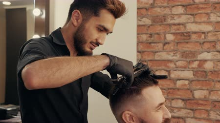 Young man getting stylish hairdo in barbershop. Haircutter combing hair and cutting hair with hairdressing scissors in male salon. Hairdresser cutting wet male hair Stock Footage