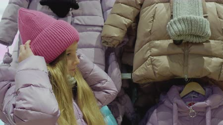 seçme : Cute little girl trying on new pink hat. Nice girl wearing winter clothing adjusting knitted hat on head. Shopping concept