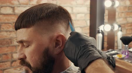 makas : Cropped shot of hairdresser cutting hair of client with scissors. Cropped shot of professional hairstylist working with man at workplace. Haircut concept Stok Video