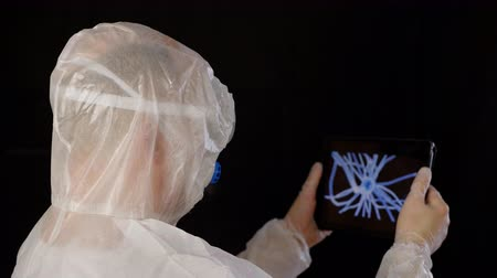 Virologist looking at virus cell on tablet screen. Back view of man wearing protective costume holding tablet and inspecting details of new bacteria. Microbiology concept Dostupné videozáznamy