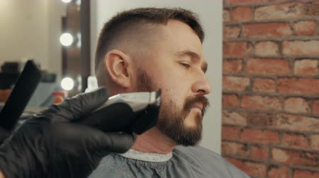 kapster : Cropped shot of barber cutting beard to satisfied client. Close-up partial view of hairdresser grooming handsome male client in barbershop. Male beauty concept Stockvideo