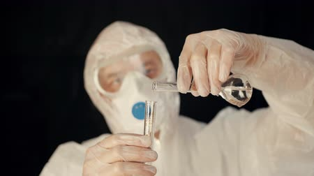 Lab worker pouring liquid into measure tube. Virologist wearing protective costume making experiment. Science concept Stock mozgókép