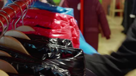 seçme : Cropped view of shop assistant arranging jackets on rack. Close up view of female hands putting warm clothing on hanger in store. Store service concept