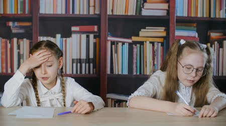жесткий : Worried girl talking and putting hands on forehead during exam. Little schoolchildren passing test. Exam failure concept