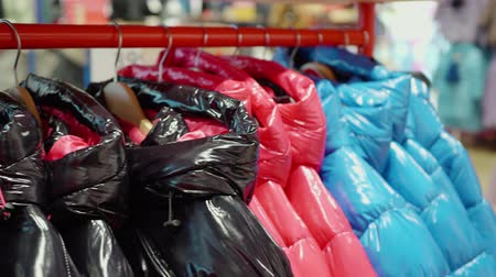 Close up view tracking shot of colorful jackets on red rack. Colorful winter clothing on hanger at store. Store concept
