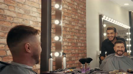 Smiling hairdresser and client looking at mirror. Satisfied cheerful mature man examining new haircut. Male beauty concept