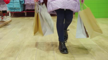 barganha : Legs shopper girl with shopping bag walking on clothes store down view. Female feet with shopping bag in fashion boutique Stock Footage