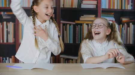 Schoolgirls having fun together on school lesson in class room. Funny teenager girl showing funny tricks with hair braids. Joyful classmates laughing on bookshelf background Stock Footage