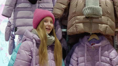sala de exposição : Teenager girl trying down jacket in clothes boutique at shopping. Happy young girl showing new down jacket in shopping store. Youth shopping in showroom Vídeos