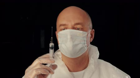 Front view of doctor releasing excess air from syringe. Man wearing protective mask preparing injection and walking to camera. Medical injection concept