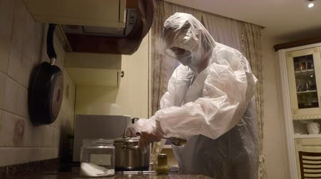 Woman wearing protective suit costume cooking at kitchen. Housekeeper adjusting facial mask and putting ingredients in pot. Prevention of disease concept