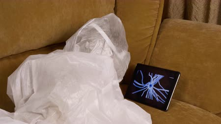 bactérias : Little girl looking at virus cell on tablet screen. Curious small scientist wearing protective costume lying on sofa with tablet PC and inspecting details of new bacteria. Concept of quarantine