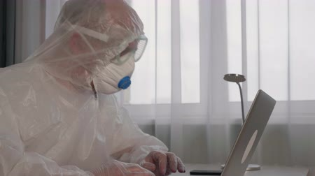 respirator : Focused virologist wearing protective suit working with laptop. Confident professional medical worker using laptop while sitting at workplace. Research concept