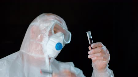 Virologist marking positive result of coronavirus test on sample shook head no. Doctor wearing protective costume holding blood sample with results and shaking head no. Coronavirus infection concept Stock Footage