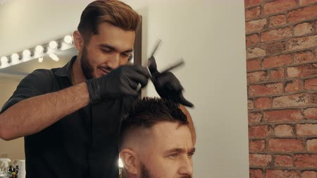 Smiling hairdresser cutting hair of client with scissors. Cropped shot of professional hairstylist working with man at workplace. Haircut concept Stock Footage