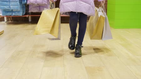 Cropped shot of girl walking with shopping bags in store. Slow motion shot of little customer strolling in shopping mall. Shopping concept Stockvideo