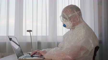 Focused virologist wearing protective suit working with laptop. Confident professional medical worker in protective costume with mask typing on laptop while sitting at workplace. Research concept